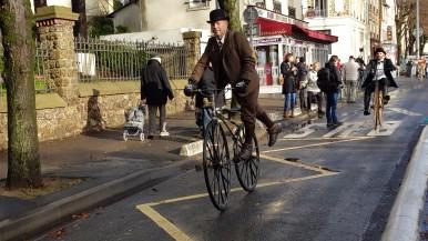"""41. 11h30 Après le passage du """"col de Chaville"""" Stuart Mason-Elliott se laisse descendre sur le marche-pied jusqu'à la mairie suivi par Robin Renard"""